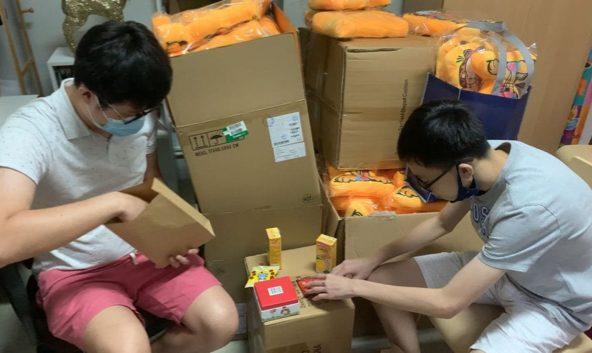 Two volunteers packing Christmas goodie bags